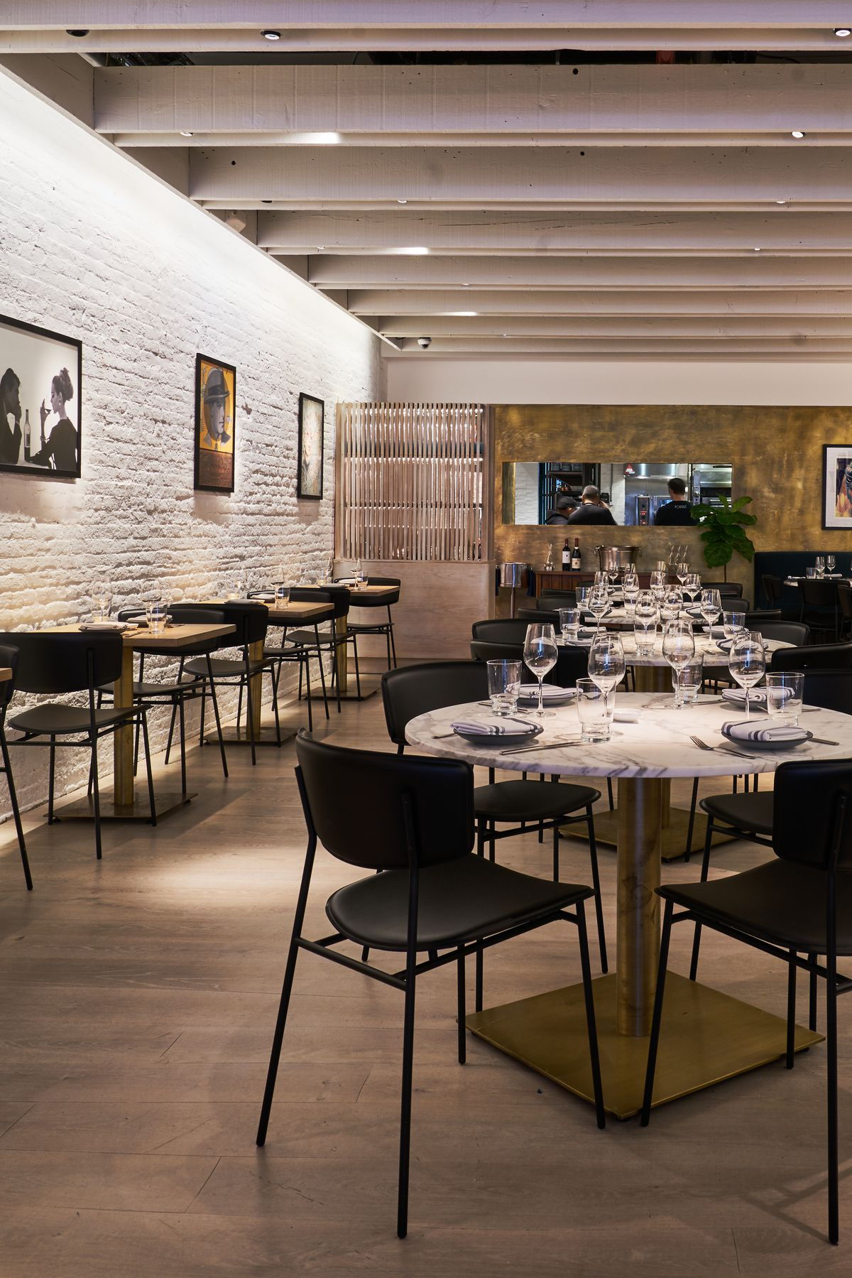 Rows of white tables with black chairs next to a white exposed brick wall