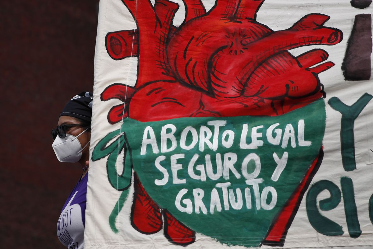 """In this Sept. 28, 2020 file photo, a woman holds a banner reading, in Spanish, """"Legal, safe, and free abortion, legalize and decriminalize abortion now, for the independence and autonomy of our bodies,"""" as abortion-rights protesters demonstrate in front of the National Congress on the """"Day for Decriminalization of Abortion in Latin America and the Caribbean,"""" in Mexico City."""