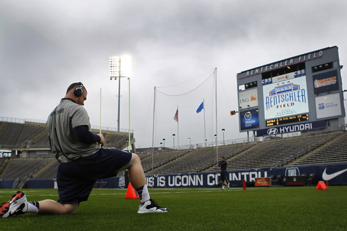 UConn offensive lineman Steve Greene stretches before a game last year in an empty stadium, which should become a familiar sight to fans soon.