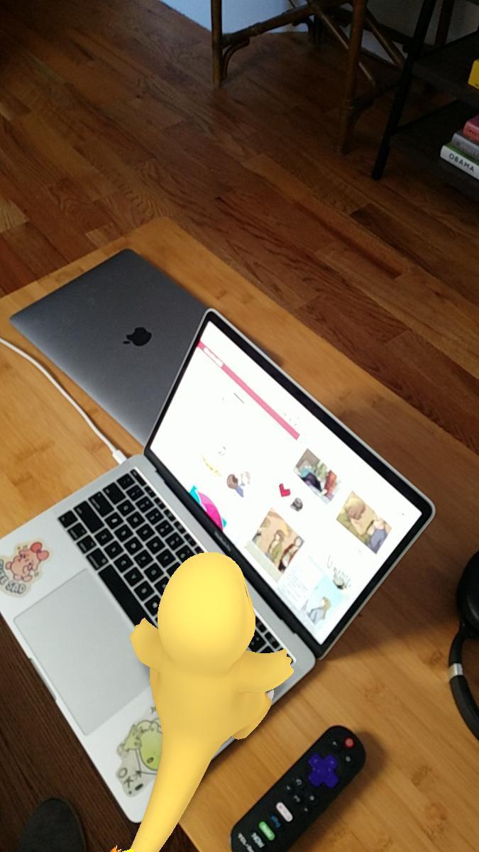 Charmander sitting on a laptop.