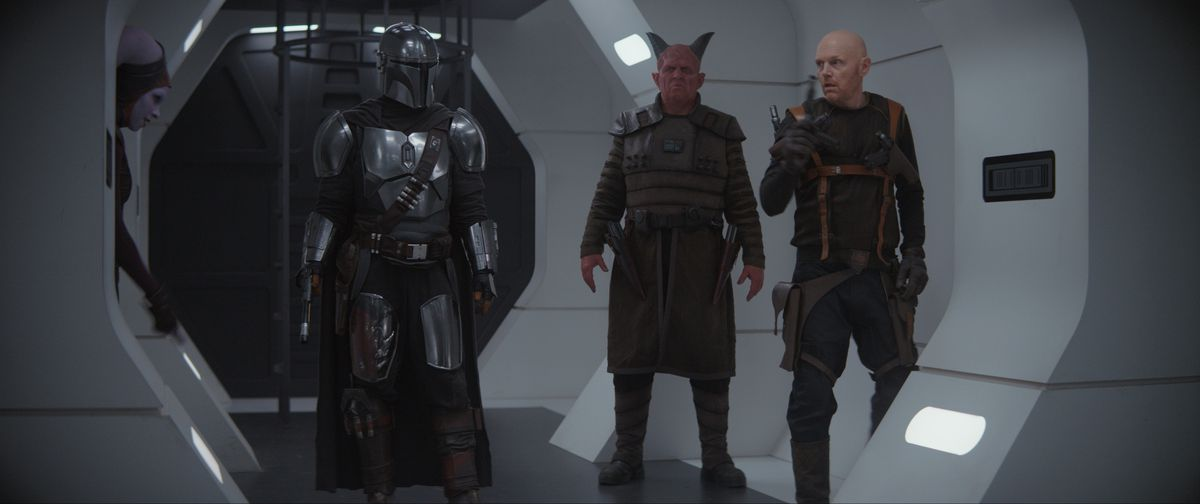 The Mandalorian and a crew of mercenaries steps aboard a white-walled New Republic prison ship, guns at the ready.