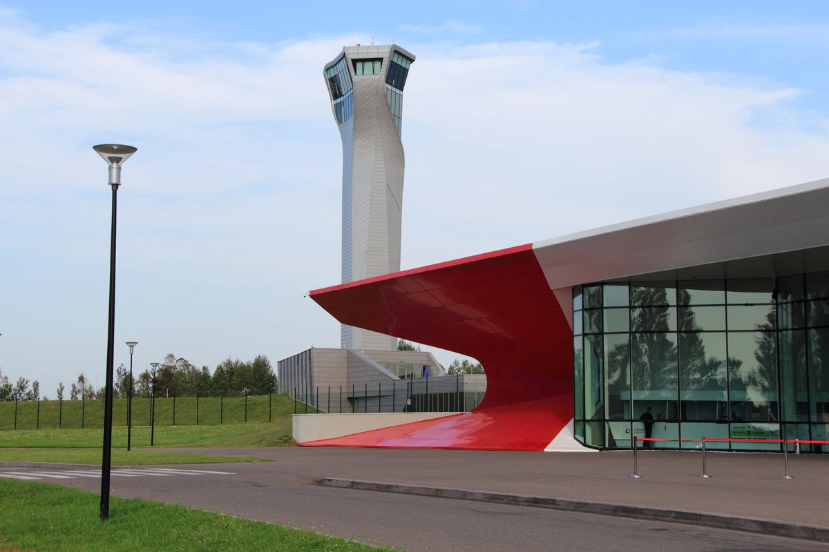 The exterior of the Kutaisi International Airport in Georgia. The facade is grey with a bright red curved design on the edge. There are windows.