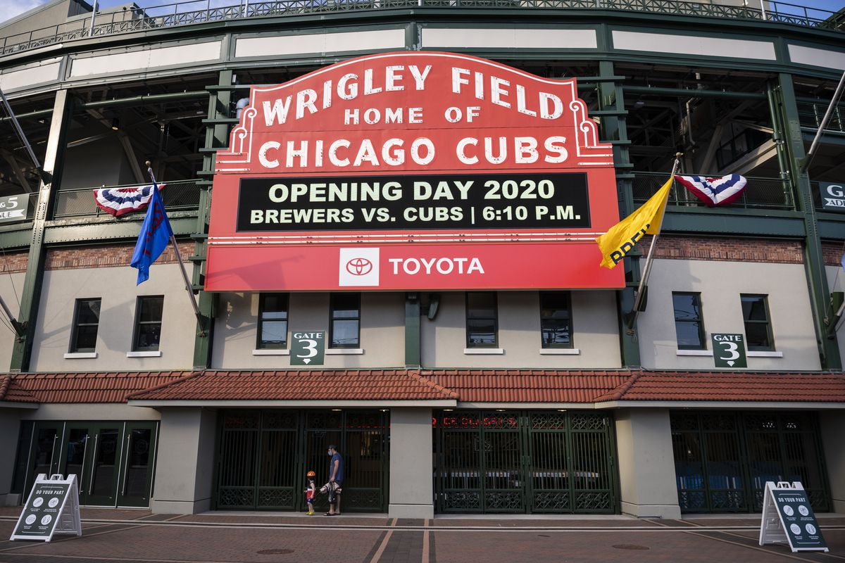 Fans walk by closed gates at Wrigley Field shortly before the start of the opening day game between the Chicago Cubs and the Milwaukee Brewers, Friday evening, July 24, 2020.