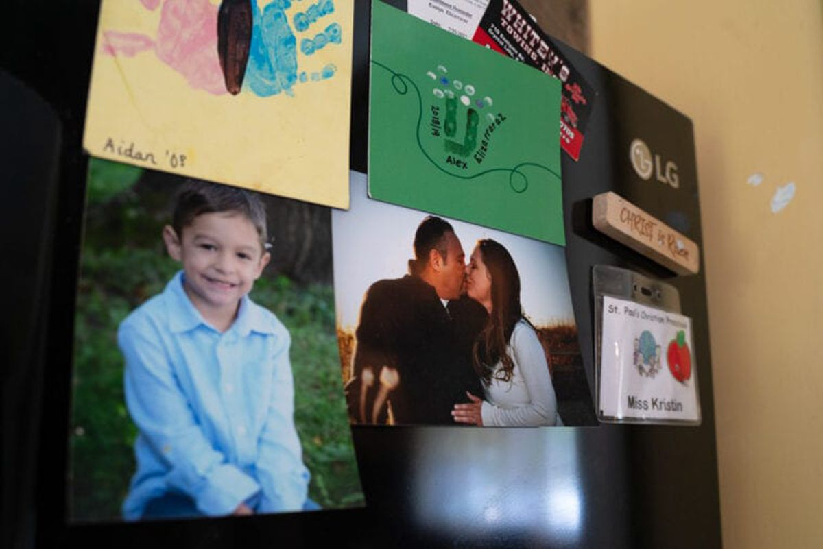 A photograph of Cesar Mauricio Elizarraraz and his fiancé Kristen Glauner hangs on their refrigerator with art made by their kids in their Crystal Lake home.