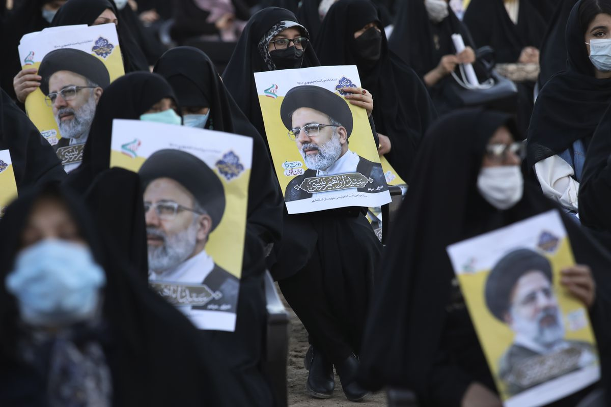 Supporters of the presidential candidate Ebrahim Raisi, currently judiciary chief, hold his posters during a campaign rally in town of Eslamshahr southwest of the capital Tehran, Iran, Sunday, June 6, 2021. Iran will hold presidential elections on June 18 with 7 candidates approved by the Guardian Council.