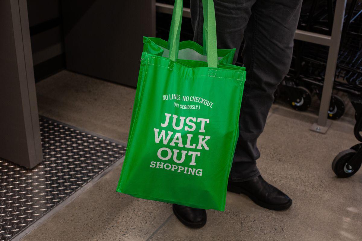 A man holds an Amazon Go bag.