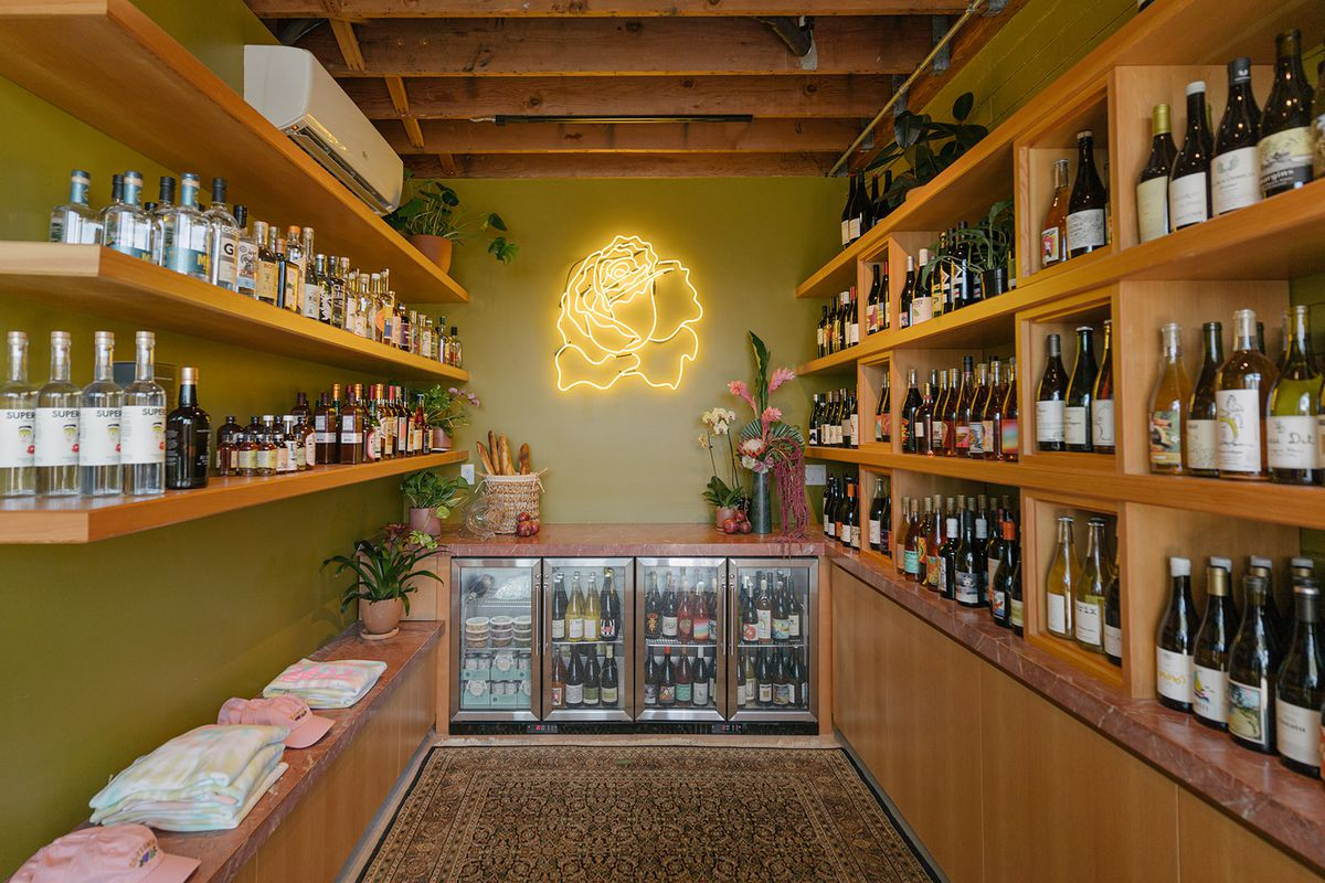 Inside Bodega Rosette there are shelves of gin and natural wine on the shelves and a cooler of chilled wine