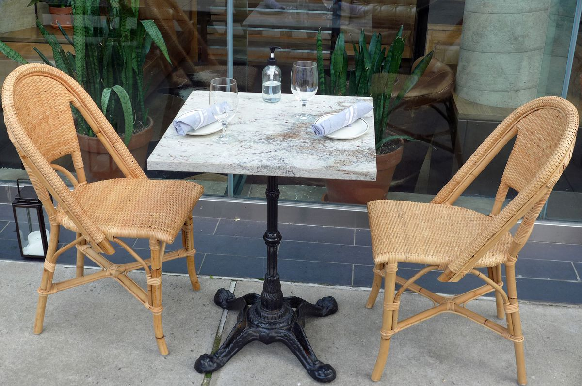A single marble topped table outdoors on the sidewalk with two chairs and two place setting and a bottle of sanitizer.