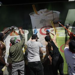 Volunteers clean graffiti from a Jamba Juice Monday, June 1, 2020, in Santa Monica, Calif., a day after unrest and protests over the death of George Floyd, a black man who died in police custody in Minneapolis on May 25.