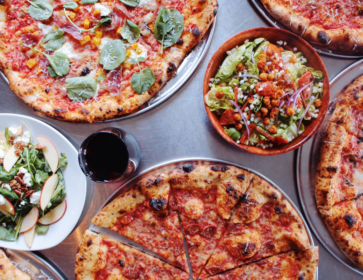 Three pizzas, two salads, and a glass of red wine from MTH Pizza in Smyrna