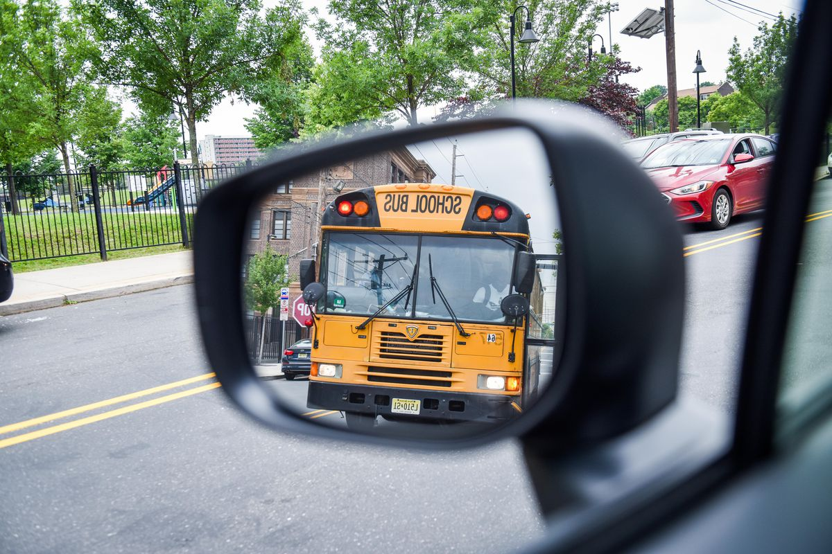 A yellow school bus is reflected in a rearview mirror as they drive down the road.