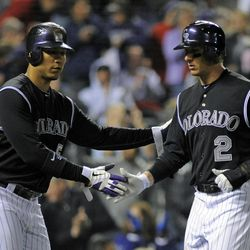 Colorado Rockies' Carlos Gonzalez (5) and Troy Tulowitzki (2) celebrate being driven in on a Todd Helton two-RBI single against the Arizona Diamondbacks during the fourth inning of a baseball game on Friday, April 13, 2012, in Denver.
