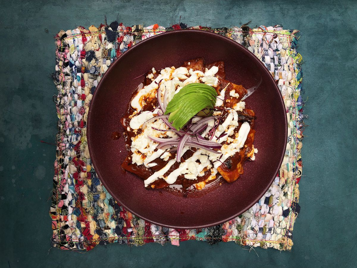 A round bowl with dark food and white sauce and a lime on a placemat.