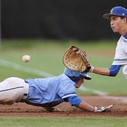 Bingham's Sean Keating looks to make a pickoff as Pleasant Grove's Walker Easton dives back to first base as Bingham and Pleasant Grove play Wednesday, May 21, 2014 in a 5A one-loss bracket game at Kearns.