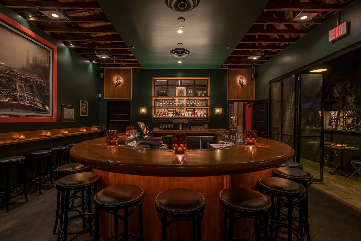 A rounded bar looks out over dark green walls and a glowing back bar.