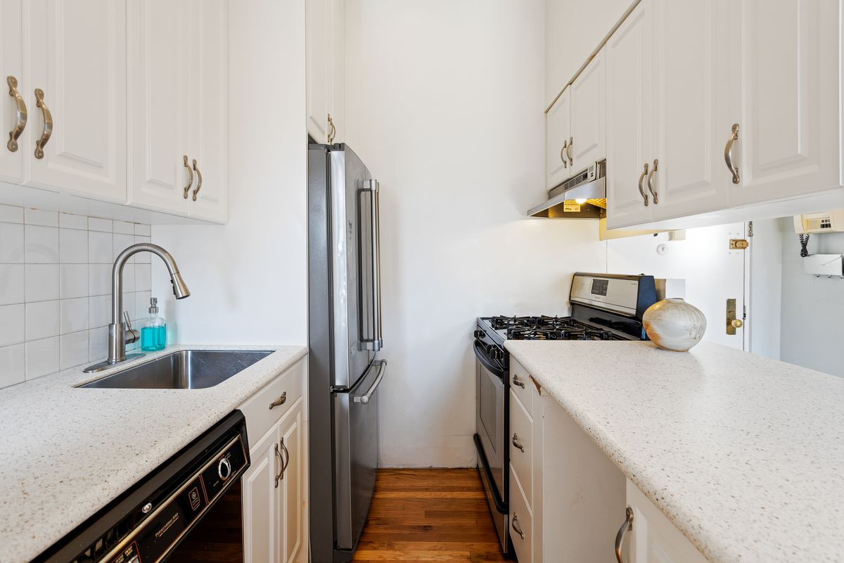 A galley kitchen features stainless steel appliances and white cabinets.