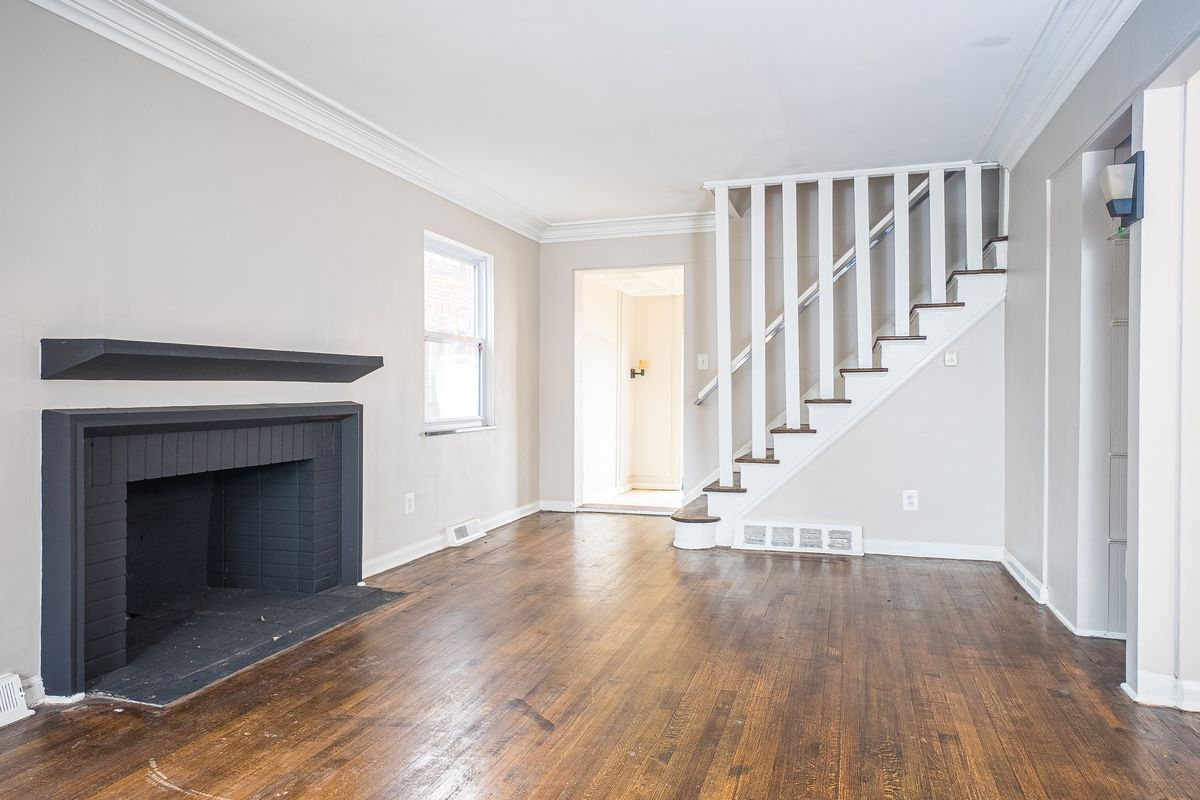 An empty room with wood floors and a fireplace with black-painted bricks. The walls are cream colored and there's stairs leading to the second floor at the other end of the room.