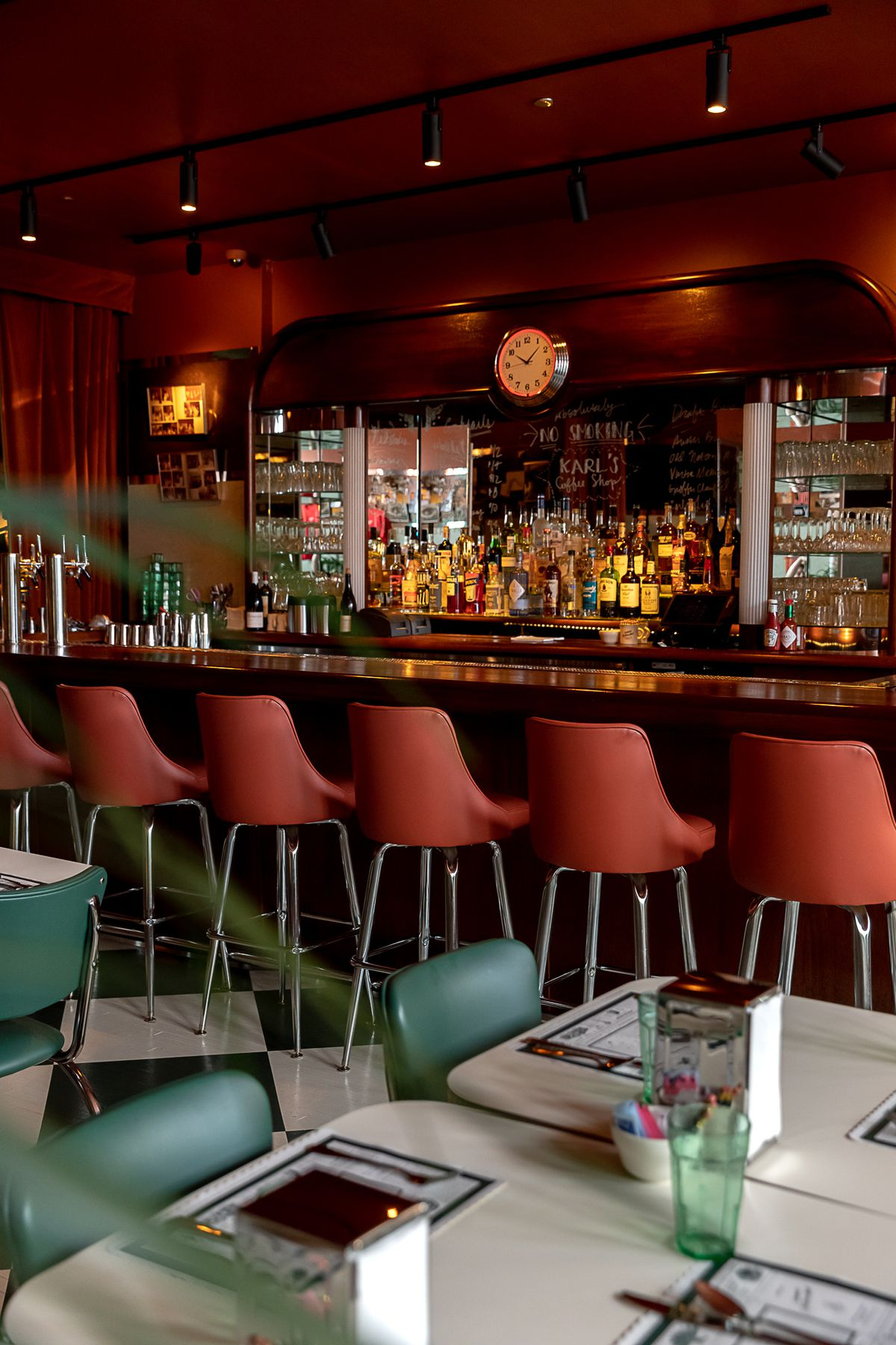 The bar at Karl's has an Art Deco aesthetic with a curved back bar and a mirror topped with a round clock and orange high backed bar stools.