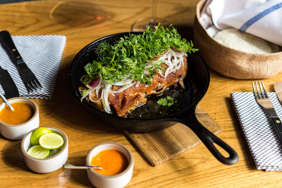 Duck carnitas at Cosme sits in a cast iron skillet underneath onions