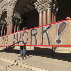 """Protesters hold a """"Back to Work"""" sign as Utahns rally against a state stay-at-home request at the City-County Building in Salt Lake City on Saturday, April 18, 2020."""