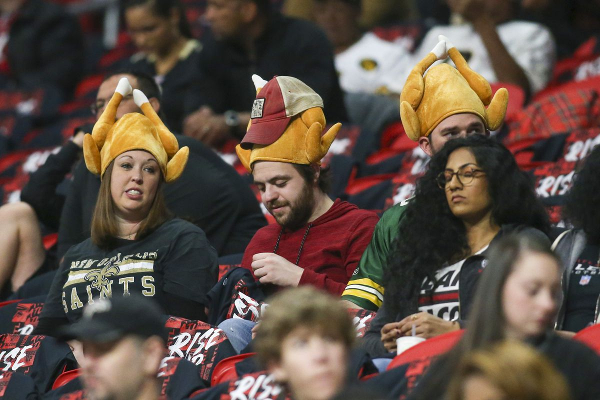 New Orleans Saints fans wear turkeys on their heads before a game against the Atlanta Falcons on Thanksgiving Day at Mercedes-Benz Stadium.
