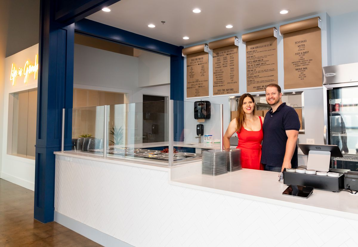 Man and woman standing behind a counter