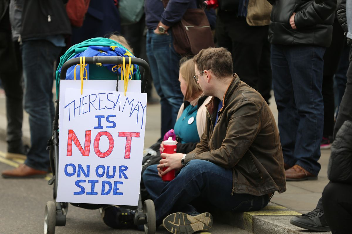 "Protesters sit next to a stroller with a sign reading ""Theresa May is not on our side"" at the People's Vote anti-Brexit march in London on March 23, 2019."