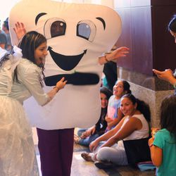 Dental student Radhee Sheth, dressed as the Tooth Fairy, tries to help children relax as Roseman University dental students provided free back-to-school dental exams for children and teens entering grades K-12 during its second annual Back to School Brush-Up event in South Jordan on Tuesday, Aug. 9, 2016.