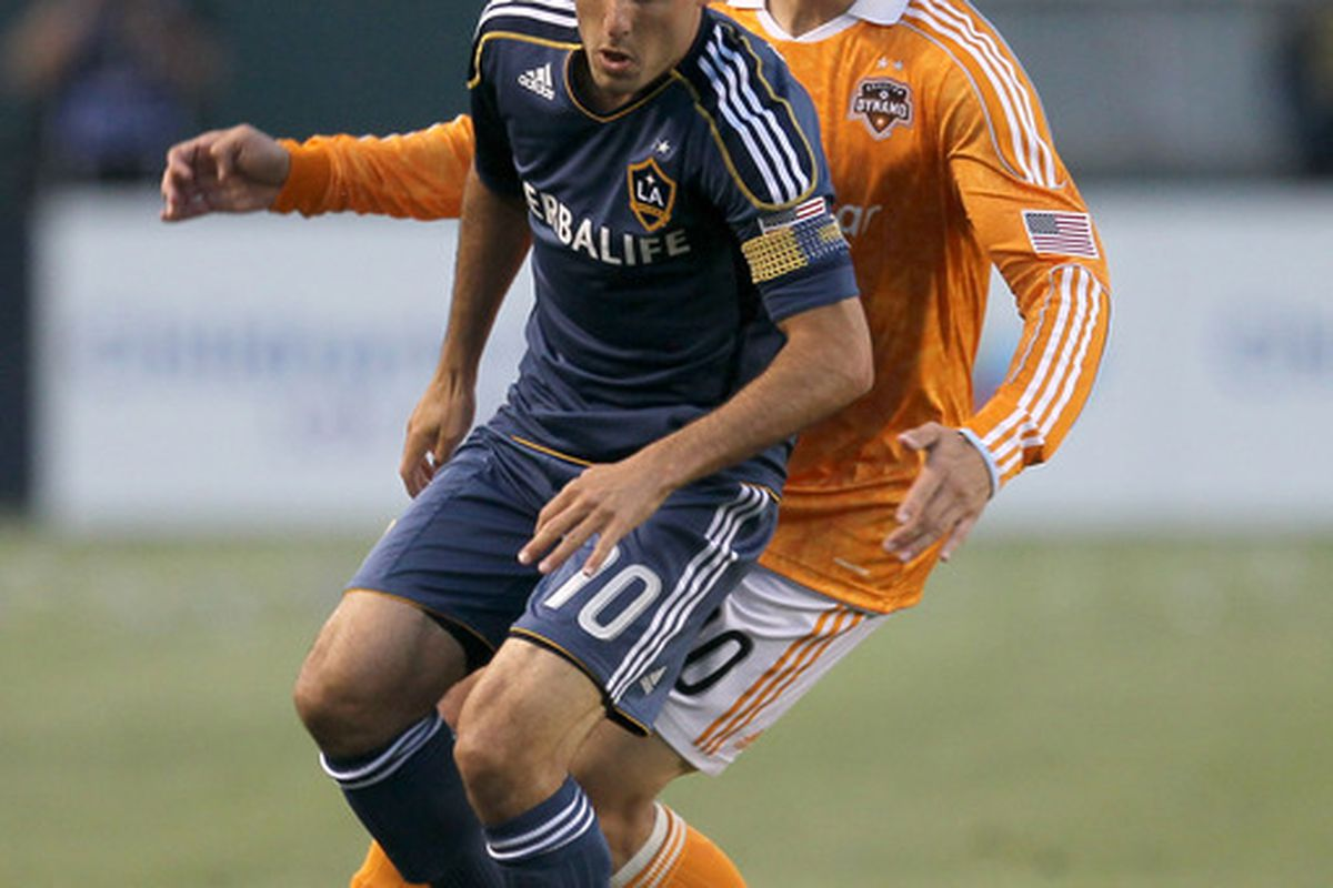CARSON, CA - MAY 25:  Landon Donovan #10 of the Los Angeles Galaxy looks for the ball in front of Geoff Cameron #20 of the Houston Dynamo at The Home Depot Center on May 25, 2011 in Carson, California.  (Photo by Stephen Dunn/Getty Images)