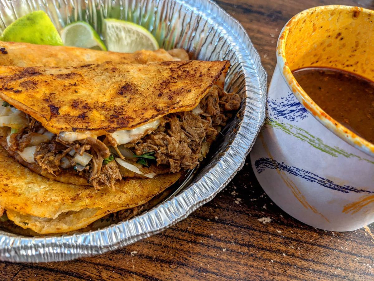 Three birria tacos in browned shells sit in a circular aluminum takeout container with lime wedges. A paper cup of reddish broth sits to the side.