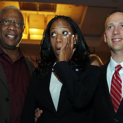 Mia Love, 4th Congressional District Republican candidate, wipes a tear as she declares victory on election night in Salt Lake City, Tuesday, Nov. 4, 2014. At left is her father, Maxime Bourdeau. At right is her husband, Jason.