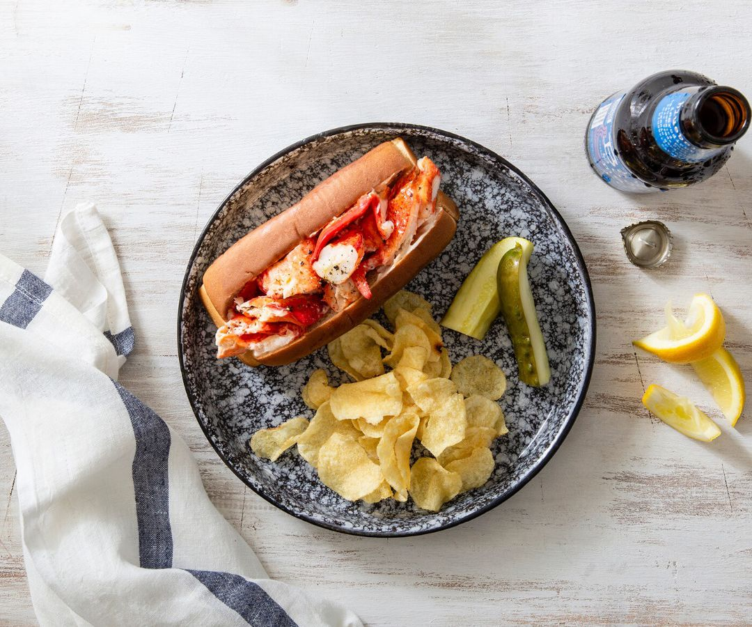 A lobster roll with chips and pickles from Mason's Famous