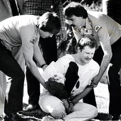 Ronnie Lee Gardner grimaces with pain from his gunshot wound on the lawn at the Metropolitan Hall of Justice after his recapture on April 2, 1985.