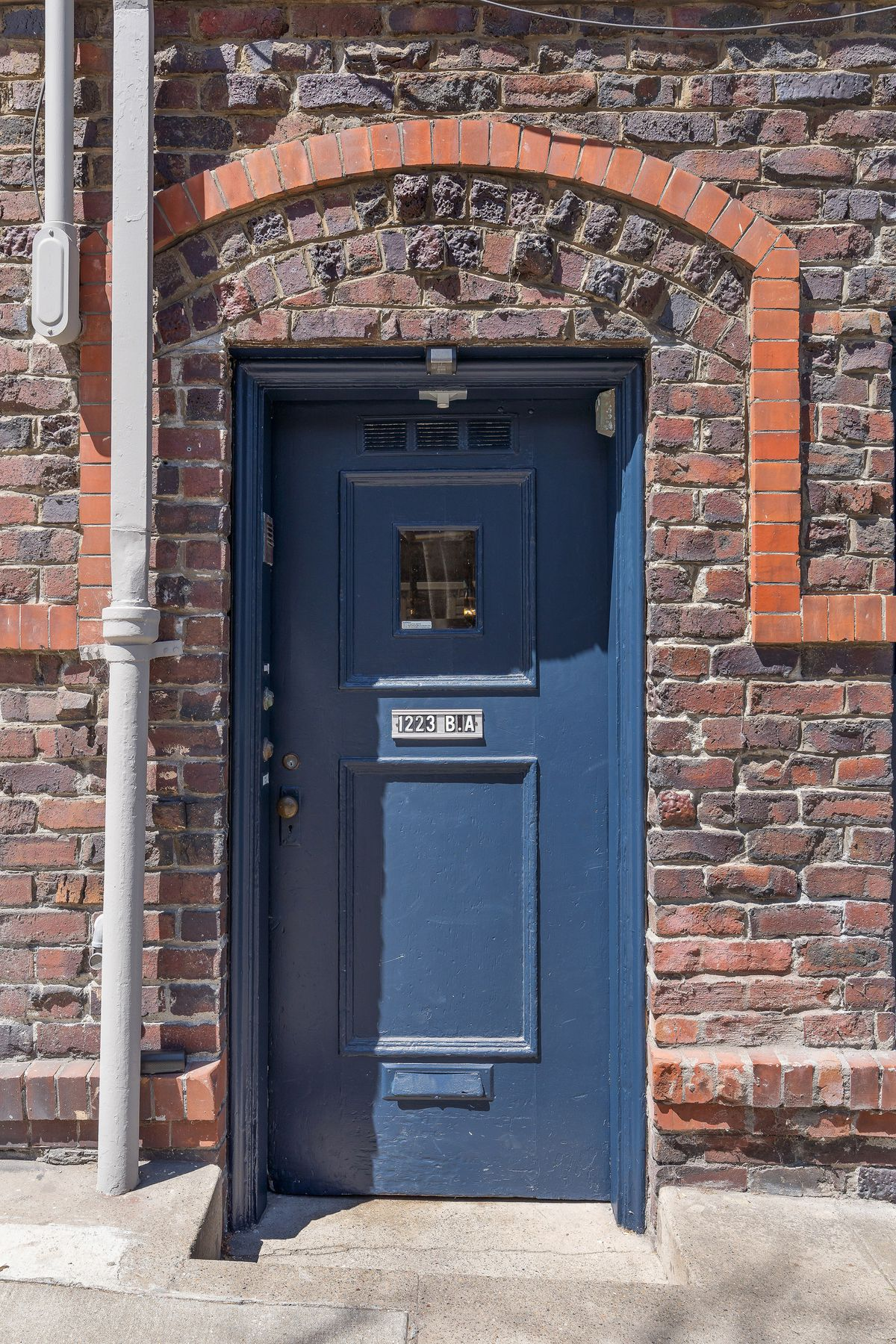 A blue door surrounded by brick that makes up the facade of the main building.
