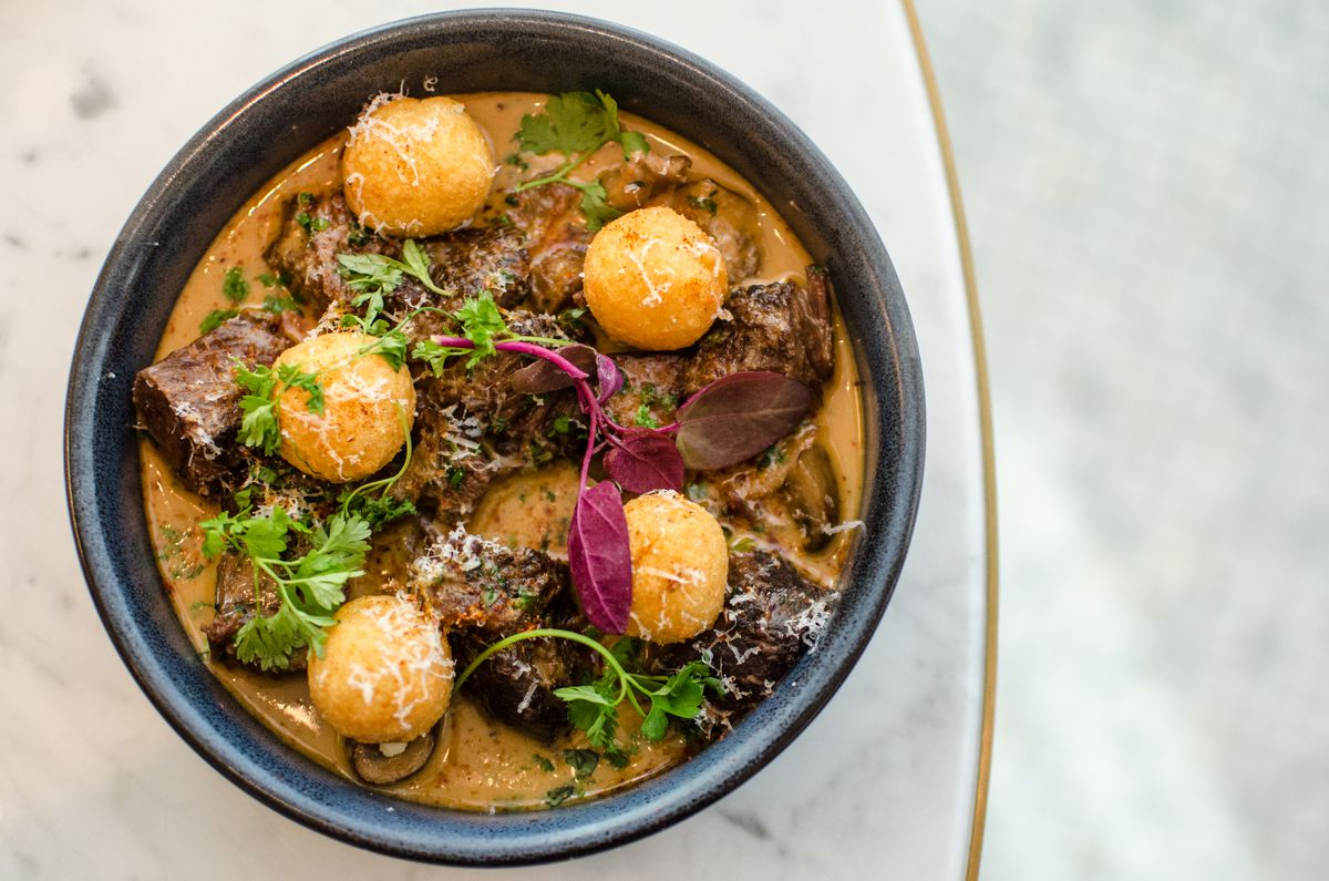 Overhead view of a round black plate with chunks of braised beef in a thick, light brown sauce, with herbs and potato balls.