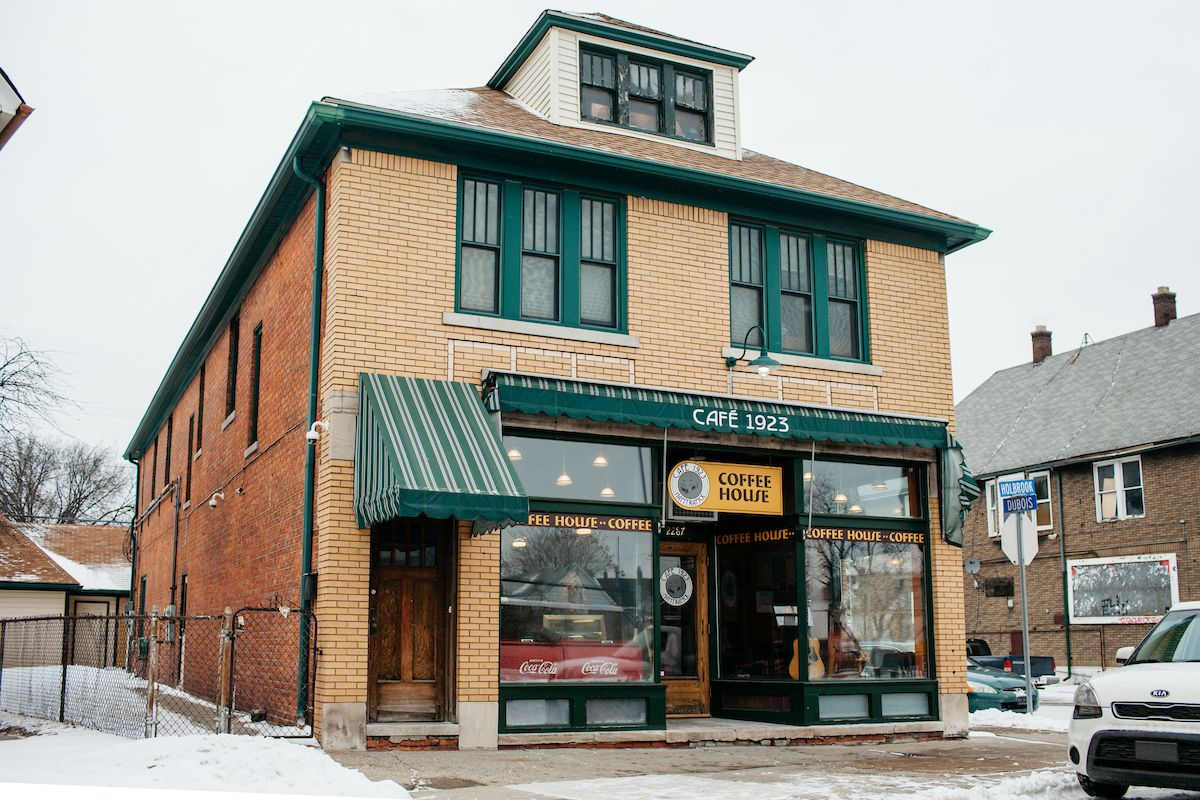 A large, two-story brick house with green awnings and a sign for Cafe 1923 shown on a snowy, cloudy day.