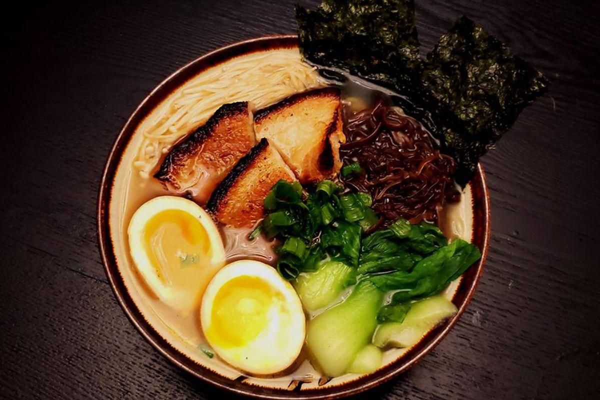 A bow of ramen with pork, bok choy, and a ramen egg split in half