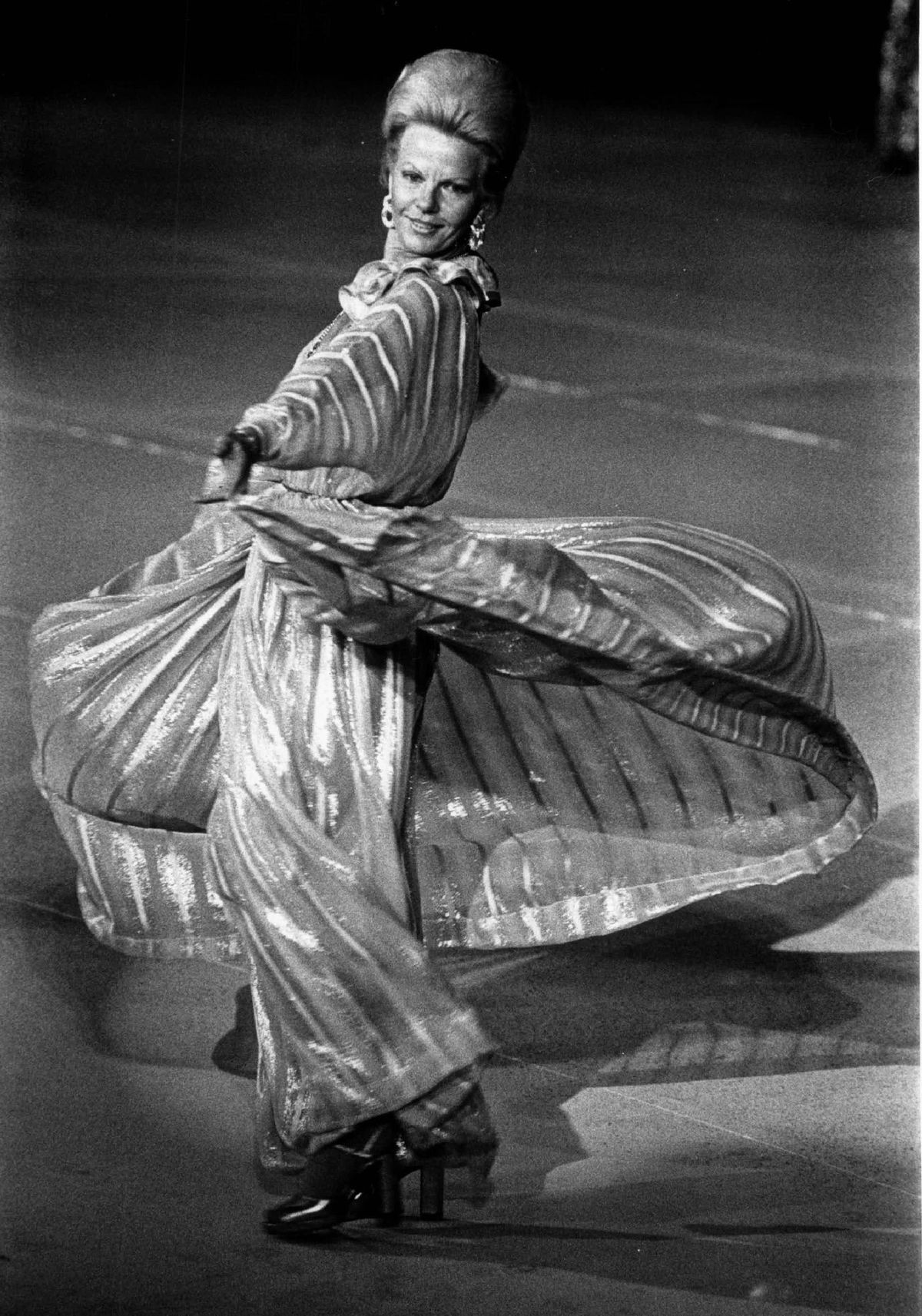Bonnie Swearingen twirling in satin stripe chiffon gown at a charity fashion event.