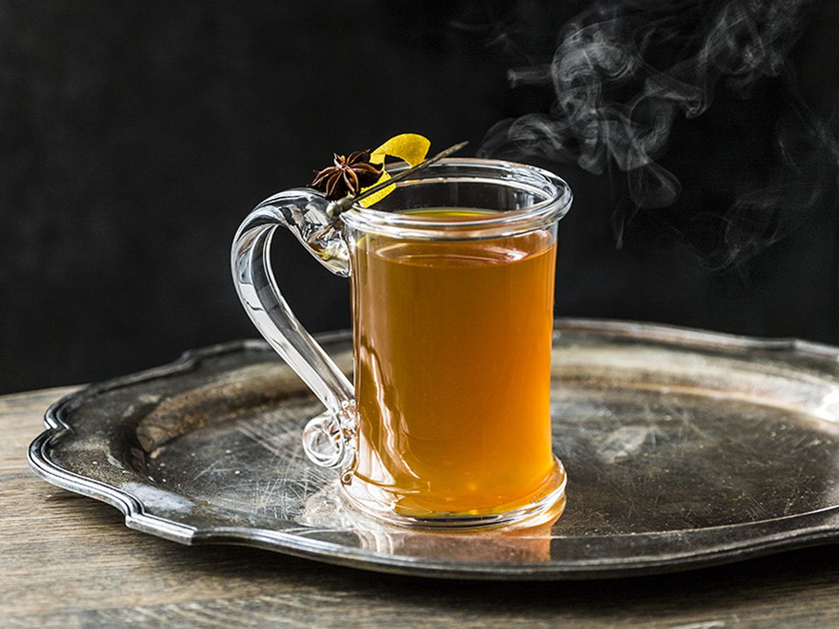 a hot toddy in a clear glass mug, garnished with a clove and lemon peel and with steam floating above it