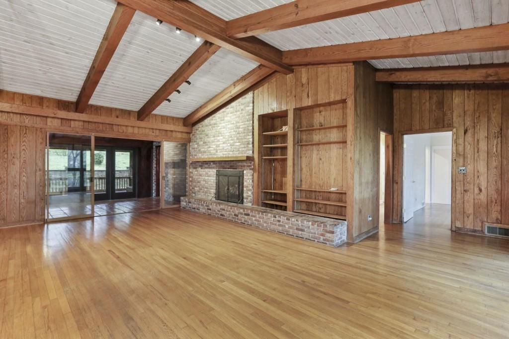 A large living room space with a big patio connected to it.