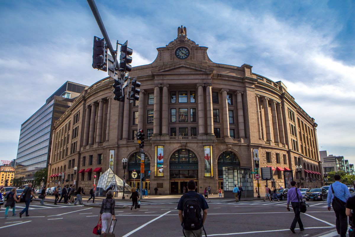A giant brown building. There is a street intersection in the foreground with people.