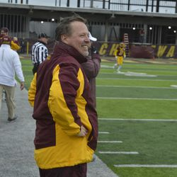 Jim McElwain, with a wet jacket, smiles at the video board as CMU wraps up the game.