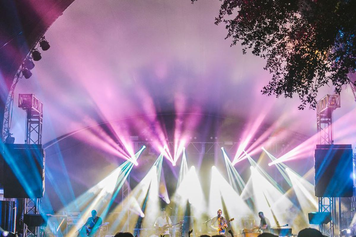 outdoor rock show with white and purple stage lights