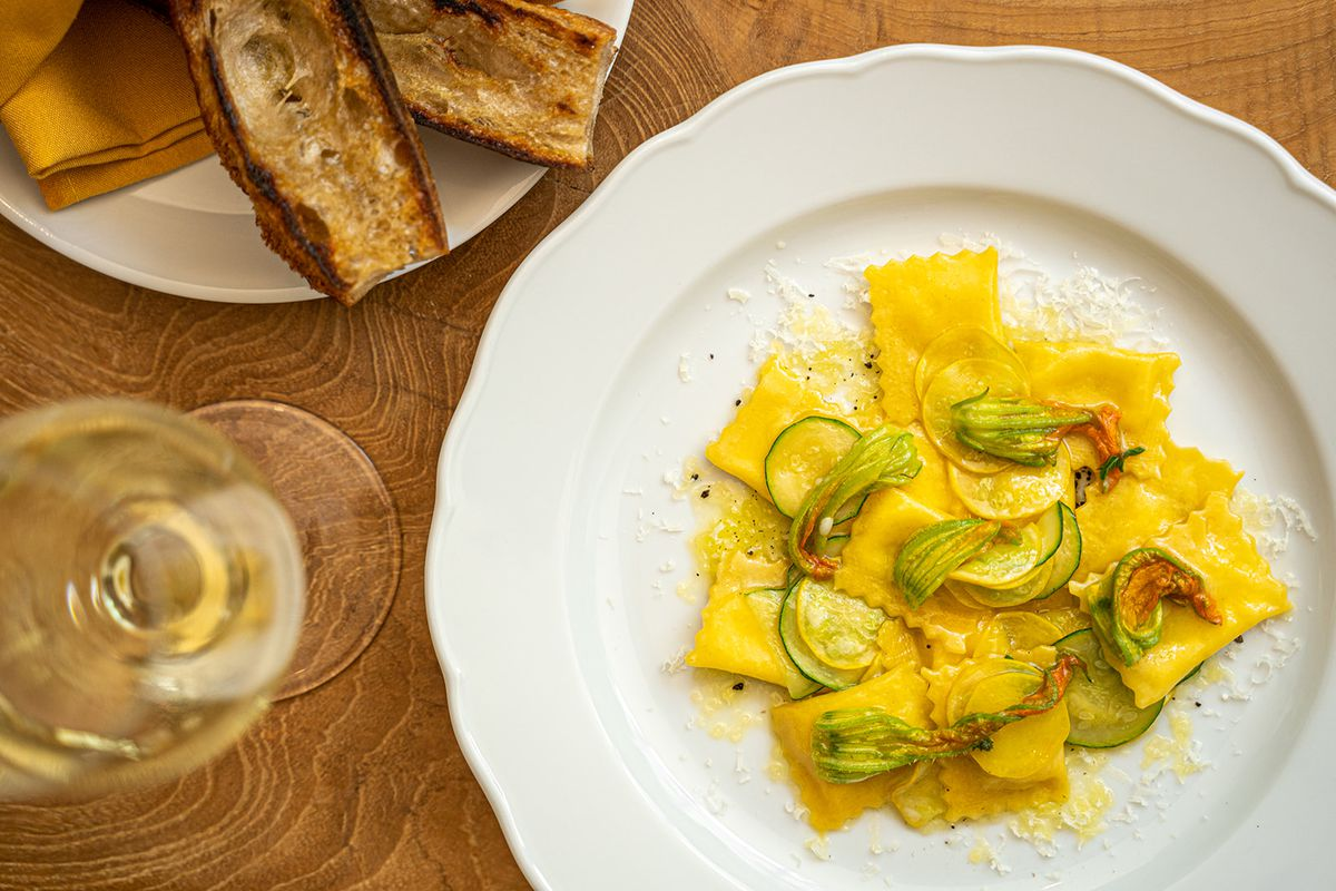 A table with a glass of wine, sliced baguette and a plate of burrata agnolini topped with zucchini blossoms