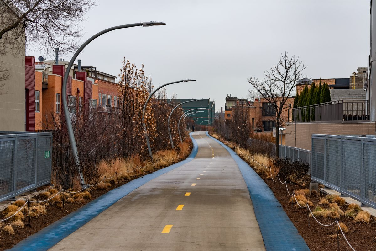 An elevated bike and jogging trail lined with bushes and wild grass, passing through a neighborhood of low-rise buildings.