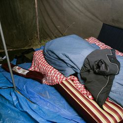Eric Richardson's inflatable mattress rests opposite of his tent mate Tyson Lloyd's bed in the tent where they live in Logan Canyon.
