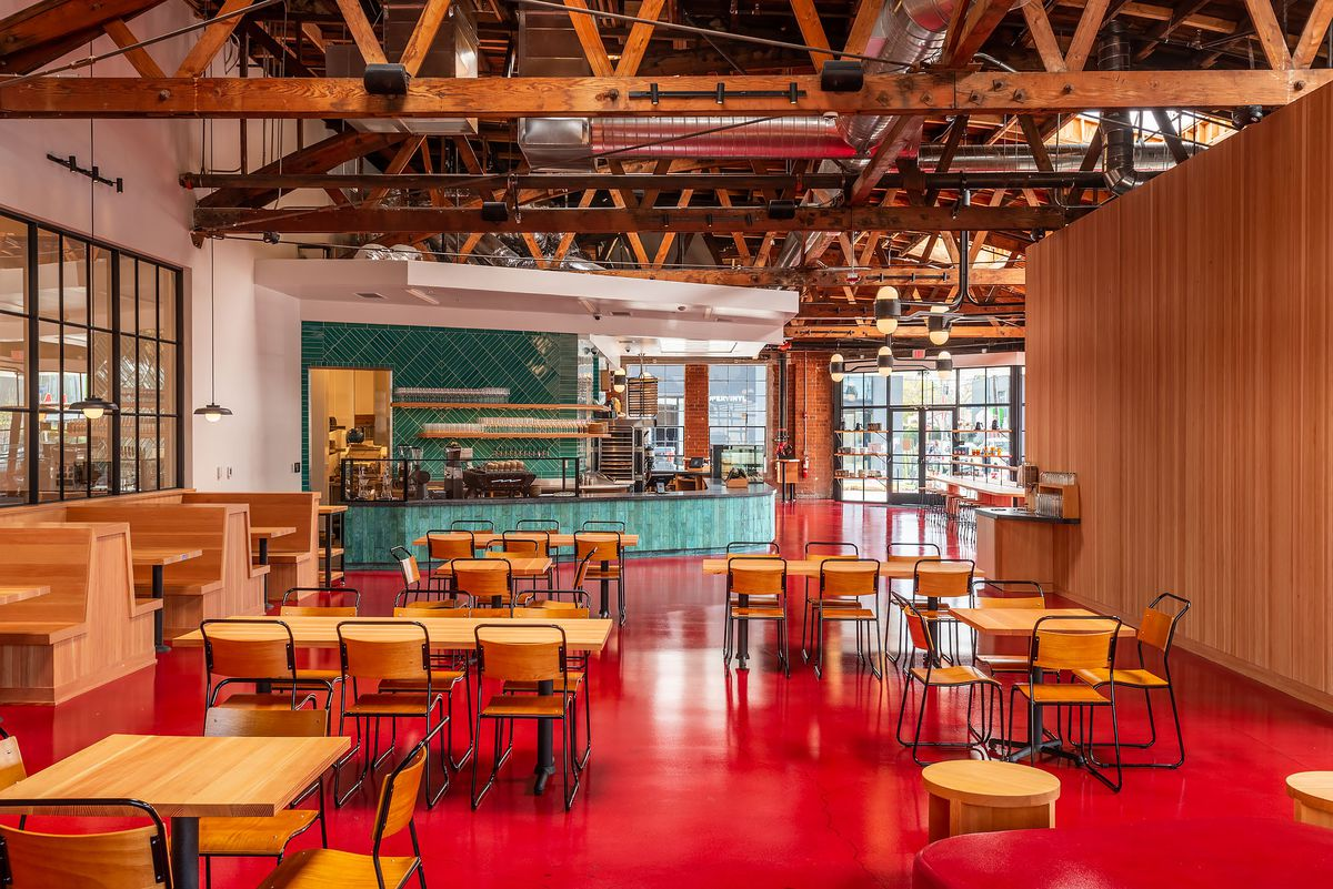 A bright cafe with red floor peeks back at a teal ordering counter.