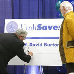 "Bishop H. David Burton of The Church of Jesus Christ of Latter-day Saints signs his Utah Saves membership card as ""Benjamin Franklin"" watches. ""Too often our wants go wild,"" Bishop Burton said."