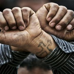 FILE - In this Friday, April 14, 2006 file photo, Egyptian Copts cross their wrists in defiance outside the Saints Church in the Sidi Bishr district of Alexandria in Egypt. Egypt's estimated 8 million Coptic Christians are feeling increasingly cornered amid the rise to power of hardline Islamists after the ouster of Hosni Mubarak's longtime authoritarian regime and fear that they will bear the brunt of blame for the film that mocked the Prophet Muhammad.
