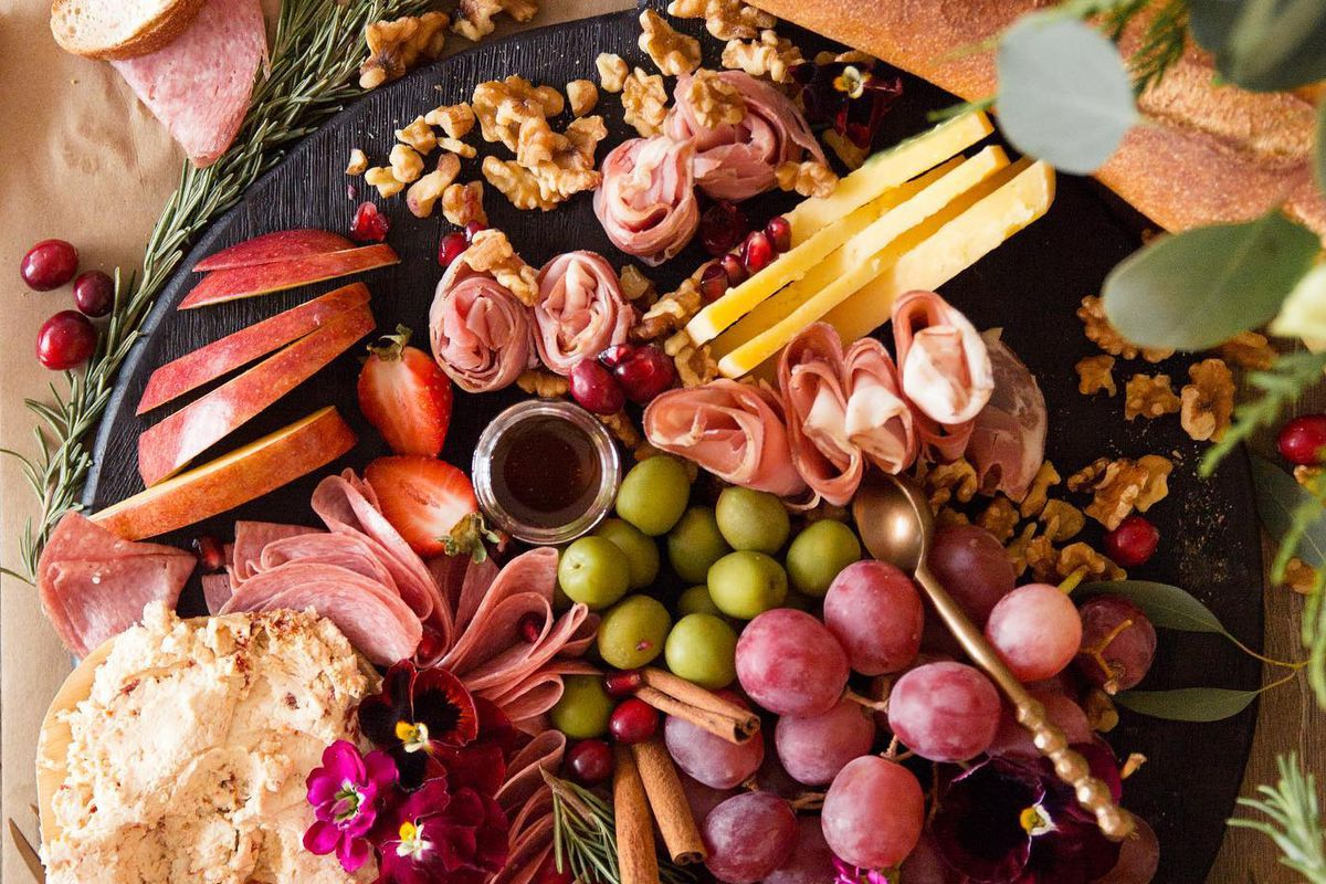 a charcuterie plate loaded with graze, baguette, cheeses, slized apples, green olives and slices of meat